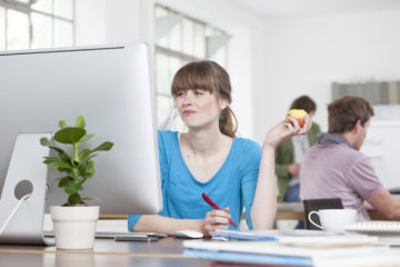 Portrait of young woman eating an apple at her desk in a creative office