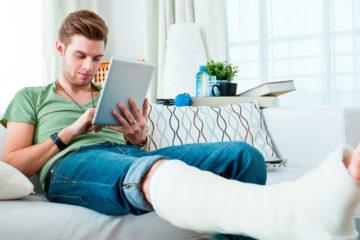Junger Mann mit gebrochenem Bein sitzt auf dem Sofa und bedient ein Tablet.